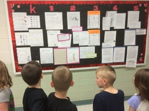Students check out our mastery wall of writing while waiting for lunch. Teacher teams selected exemplary pieces of work at the mid-year point.